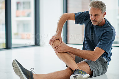 Buy stock photo Shot of an uncomfortable looking middle aged man touching his knee due to pain while being seated on the floor of a fitness studio during the day