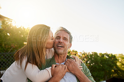 Buy stock photo Cropped shot of a beautiful mature woman kissing her handsome husband outside