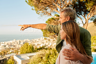 Buy stock photo Cropped shot of a handsome mature man pointing out something to his beautiful wife outdoors