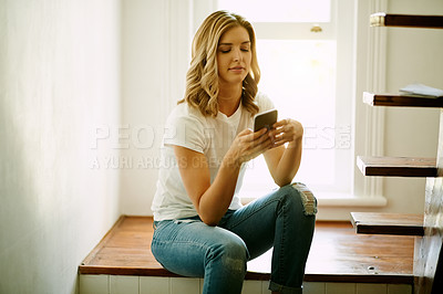 Buy stock photo Shot of an attractive young woman using a mobile during a relaxing day at home