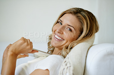 Buy stock photo Portrait of an attractive young woman holding a digital tablet while relaxing on the sofa at home