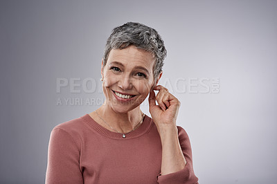 Buy stock photo Studio portrait of a confident mature woman posing against a gray background