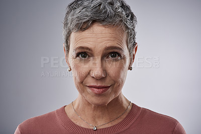 Buy stock photo Studio portrait of a mature woman posing against a gray background