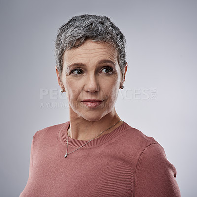 Buy stock photo Studio shot of a mature woman looking thoughtful against a gray background