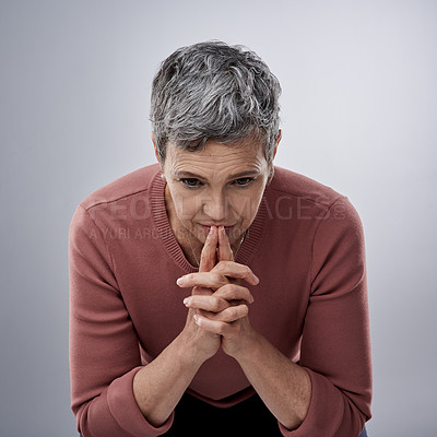 Buy stock photo Studio shot of a mature woman looking serious against a gray background