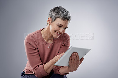 Buy stock photo Studio shot of a mature woman using a digital tablet against a gray background