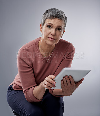 Buy stock photo Studio portrait of a mature woman using a digital tablet against a gray background