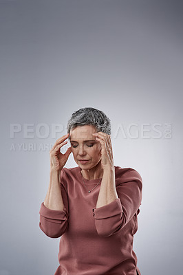 Buy stock photo Studio shot of a mature woman experiencing a headache against a gray background
