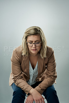 Buy stock photo Studio shot of an attractive young businesswoman looking sad against a gray background