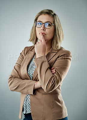 Buy stock photo Studio shot of an attractive young businesswoman looking thoughtful against a gray background