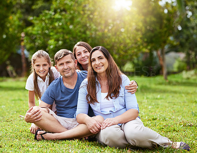Buy stock photo Portrait of a cheerful young family seated in a park together outside during the day