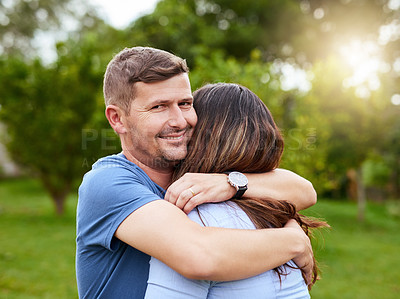 Buy stock photo Portrait of a cheerful young man giving his wife a hug while standing in a park outside during the day