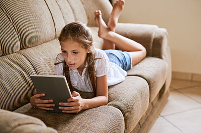 Buy stock photo Shot of a focussed young girl browsing on a digital tablet while lying on a sofa at home during the day