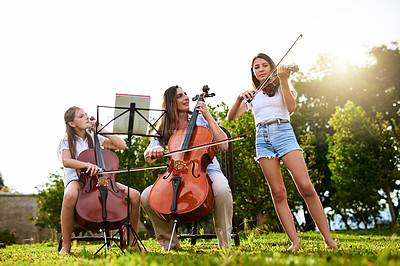 Buy stock photo Shot of a cheerful young mother and her two daughters playing classical string instruments together while standing in the backyard of their home