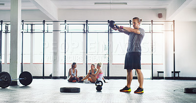 Buy stock photo Shot of a young man working out with kettle bells in a gym