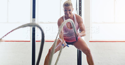 Buy stock photo Shot of a young woman working out with battle ropes in a gym