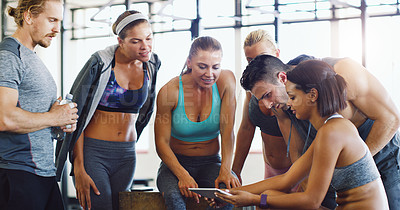 Buy stock photo Shot of a group of happy young women using a digital tablet together in a gym