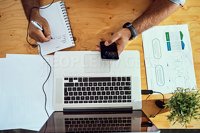 Buy stock photo High angle shot of an unrecognizable businessman working at his desk in an office