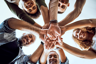 Buy stock photo Low angle shot of a group of businesspeople joining their hands together in a huddle