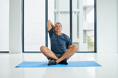 Buy stock photo Shot of a focused middle aged man seated on a exercise mat on the floor while doing stretching exercises inside of a fitness studio