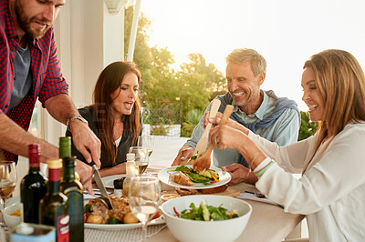 Buy stock photo Shot of a group of cheerful people having dinner together around a table outside at a restaurant