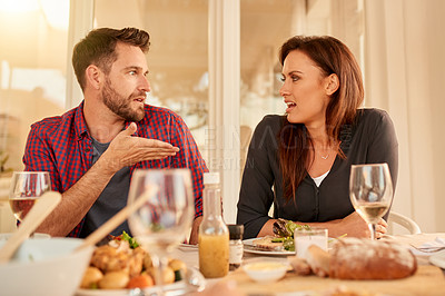 Buy stock photo Shot of a young couple having dinner together around a table while talking to each other at home