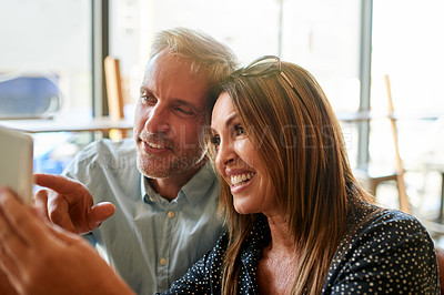 Buy stock photo Shot of a happy mature couple using a digital tablet together at a cafe