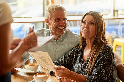 Buy stock photo Shot of a mature couple giving a waitress their order in a cafe