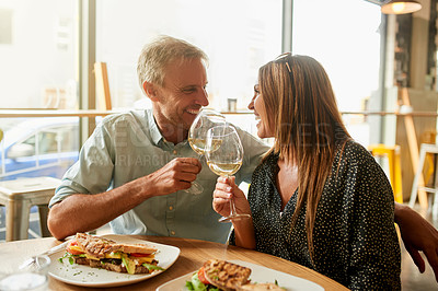 Buy stock photo Shot of a mature couple enjoying some wine together with their meal at a restaurant