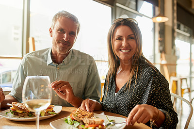 Buy stock photo Shot of a mature couple enjoying a meal together at a restaurant