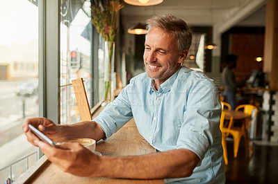 Buy stock photo Shot of a mature man using a mobile phone at a cafe