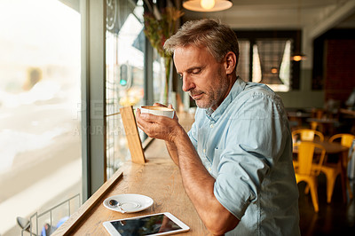 Buy stock photo Shot of a mature man looking at his mobile phone while having coffee at a cafe