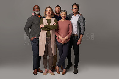 Buy stock photo Studio shot of a group of people posing together against a gray background