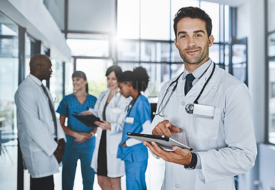 Buy stock photo Portrait of a young doctor using a digital tablet in a hospital with his colleagues in the background