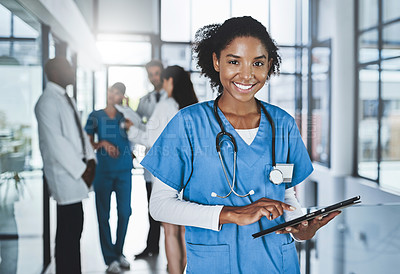 Buy stock photo Portrait of a young doctor using a digital tablet in a hospital with her colleagues in the background