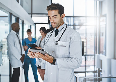 Buy stock photo Shot of a young doctor using a digital tablet in a hospital with his colleagues in the background