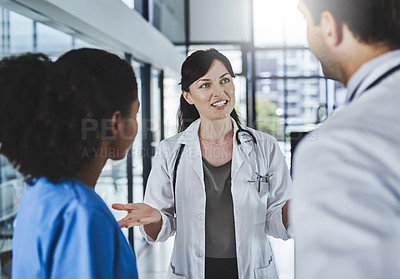Buy stock photo Shot of a team of doctors having a discussion in a hospital
