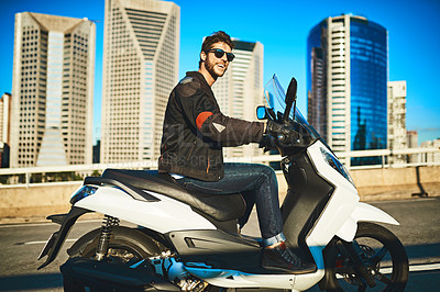 Buy stock photo Shot of a young man riding a motorbike through the city