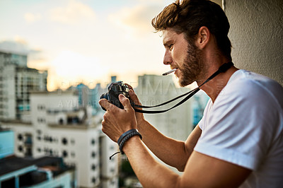 Buy stock photo Cropped shot of a young man taking photographs of the city with a camera outside