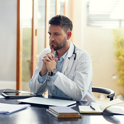 Buy stock photo Cropped shot of a handsome male doctor looking thoughtful while sitting in his office