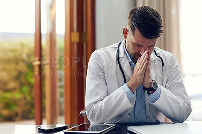 Buy stock photo Cropped shot of a handsome male doctor praying while sitting in his office