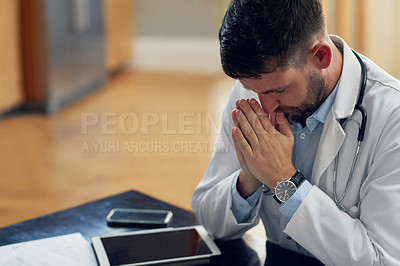 Buy stock photo High angle shot of a handsome male doctor praying while sitting in his office
