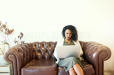 Buy stock photo Shot of a woman sitting on the sofa with her laptop