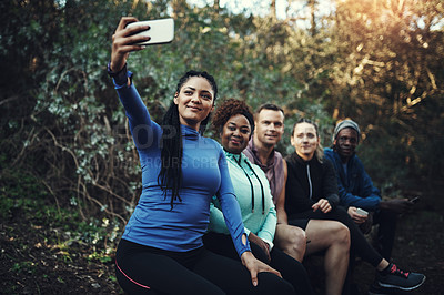 Buy stock photo Cropped shot of a sporty young group of friends taking a selfie while taking a break during a workout in the forest