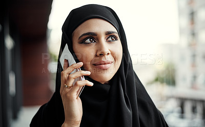 Buy stock photo Cropped shot of an attractive young businesswoman dressed in Islamic traditional clothing making a phonecall while standing on her office balcony