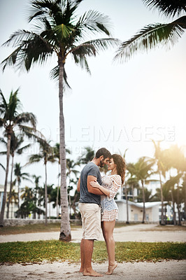 Buy stock photo Shot of a young couple spending a romantic day at the beach