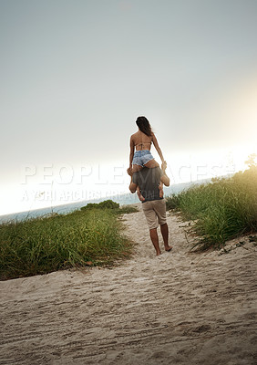 Buy stock photo Rearview shot of a happy young couple having fun at the beach