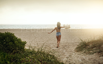 Buy stock photo Rearview shot of a happy young woman enjoying a day at the beach
