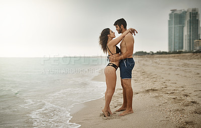 Buy stock photo Shot of a young couple enjoying a beach getaway