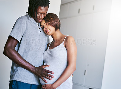 Buy stock photo Shot of a young man touching his pregnant wife's belly